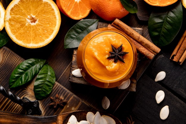Стакан тыквенных и оранжевых смузи со специями на черном деревянном столе. фото высокого качества