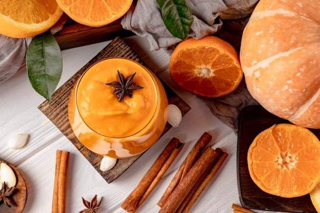 Стакан тыквенных и апельсиновых коктейлей со специями на столе, вид сверху. фото высокого качества