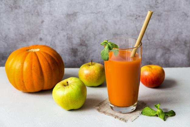 ミントの葉と灰色の背景に飲用チューブと果物で飾られたカボチャのリンゴジュースのガラス