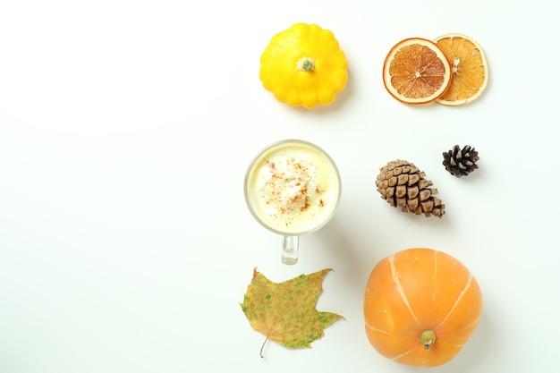 Стакан тыквенного латте и ингредиенты на белом фоне