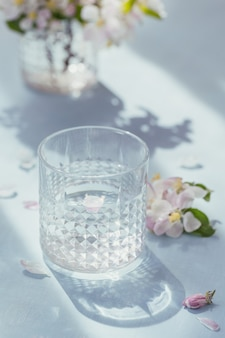ガラスの中に開花するリンゴの木の枝が付いているテーブルの上の純粋な水のガラス。朝の陽射しムード