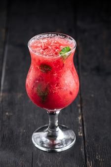Стакан коктейля из красных ягод на деревянных фоне