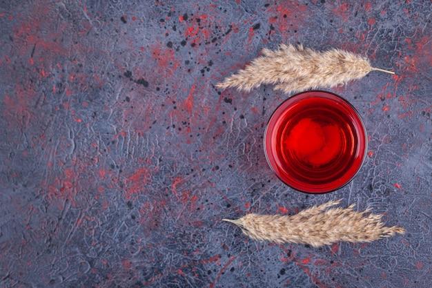 Стакан красного коктейля с кусочками фруктов на мраморе.