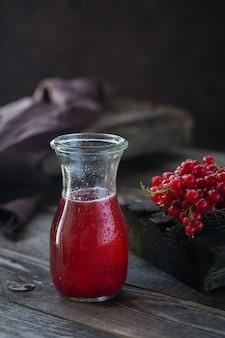 赤スグリのカクテルまたはモクテルのグラス、砕いた氷とダークウッドのスパークリングウォーターでさわやかな夏の飲み物