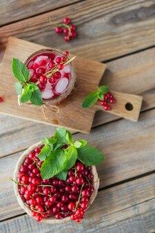 赤スグリのカクテルまたはモクテルのグラス、砕いた氷と木の表面にスパークリングウォーターでさわやかな夏の飲み物