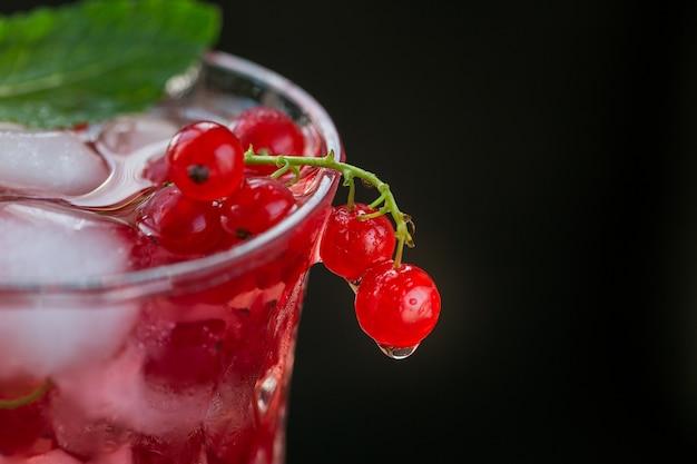 赤スグリのカクテルまたはモクテルのグラス、砕いた氷と暗い木製のテーブルの上のスパークリングウォーターでさわやかな夏の飲み物