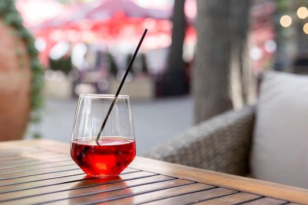 여름 테라스에 있는 나무 테이블에 빨간 주스 한 잔.