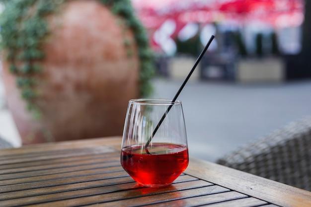 햇빛 아래 나무 테이블에 빨간 주스 한 잔.
