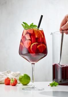 軽い台所のテーブルの上の赤いサングリアのガラス