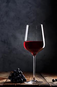 Стакан красного вина и гроздь винограда на старый деревянный стол.
