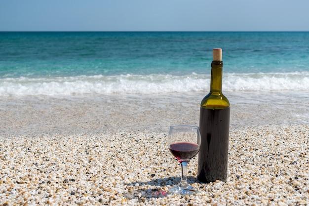 Бокал красного вина и бутылка на пляже в солнечный летний день
