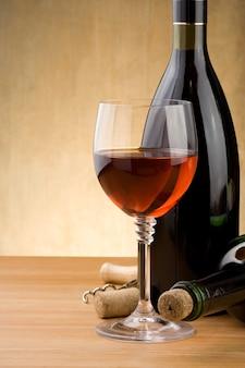 赤ワインのガラスと木の背景にブドウとボトル