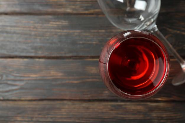 Бокал красного вина и пустой стакан на деревенском деревянном фоне