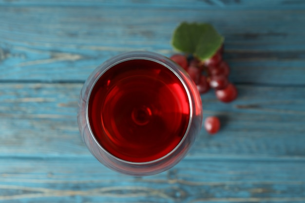 木製のテーブルに赤ワインとブドウのガラス