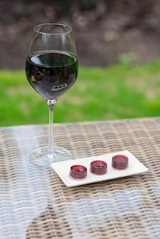 テーブルの上の赤ワインとマーマレードワインキャンディーのガラス。自家製マーマレード。