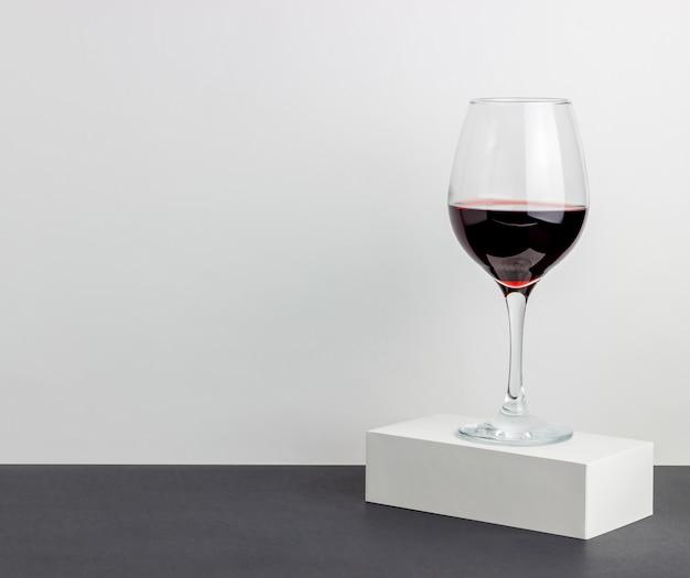 白いテーブルに赤ワインのガラス。ミニマリズム。