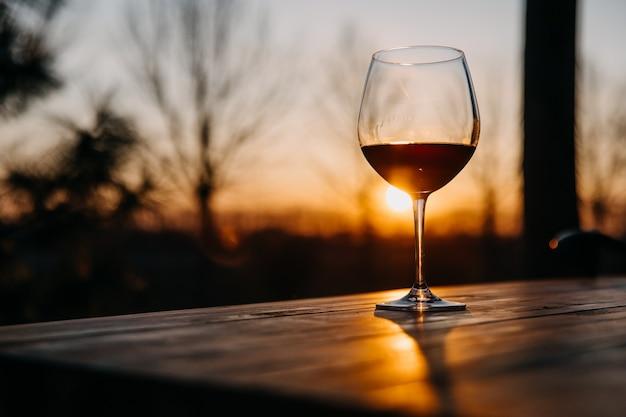 日没時のテラスで木製のテーブルに赤ワインのグラス