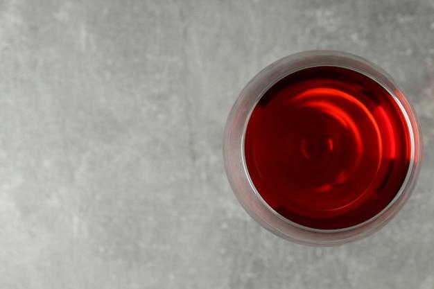 灰色のテクスチャ背景に赤ワインのガラス