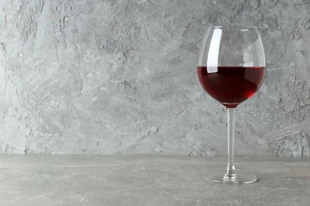 灰色の織り目加工のテーブルに赤ワインのガラス