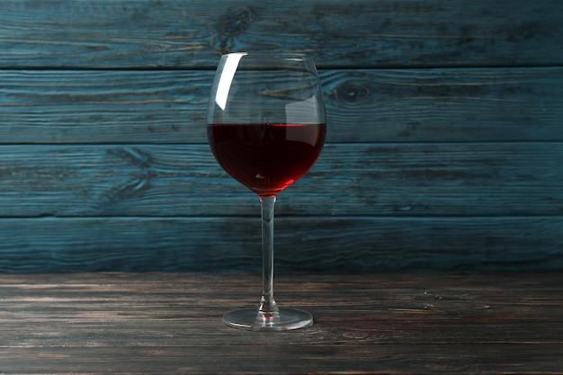 素朴な木製の背景に赤ワインのガラス