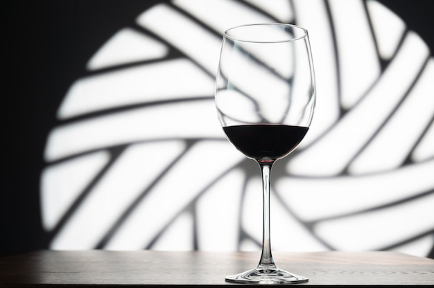 Бокал красного вина на пространстве декоративного круглого окна