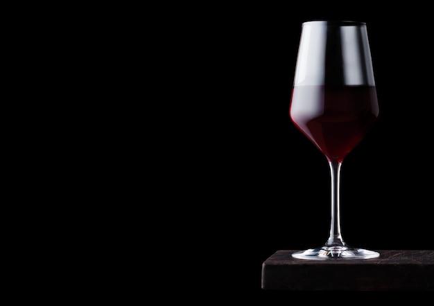黒いテーブルの上の木の板に赤ワインのガラス。