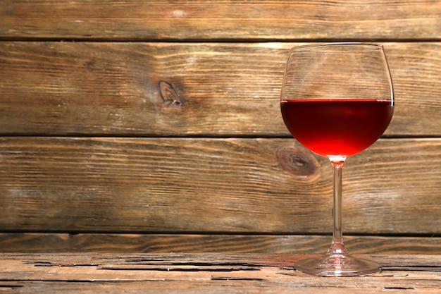 Бокал красного вина на деревянном столе на деревянной стене