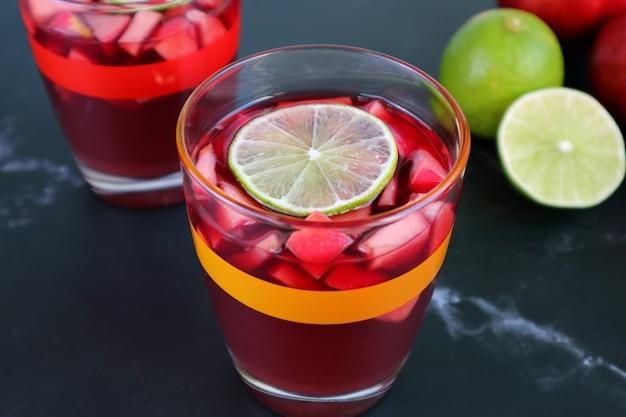 ぼやけた別のグラスとライムと赤ワインサングリアのグラス