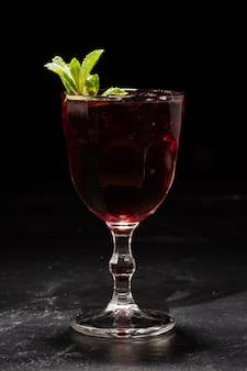 黒の背景にミントの葉と赤ワインサングリアのガラス