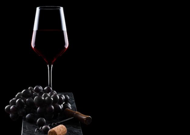 Стакан красного вина с темным виноградом и старинным штопором и пробкой