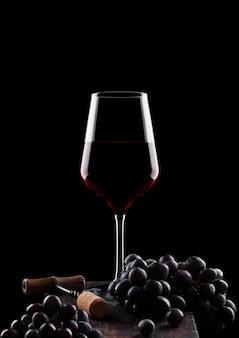 Стакан красного вина с темным виноградом и старинным штопором