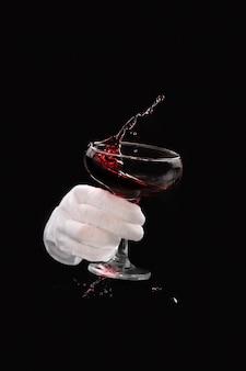 날아다니는 적포도주 한 잔이 검은 배경에 흰 장갑을 낀 웨이터의 손으로 음료를 쏟고 있습니다.