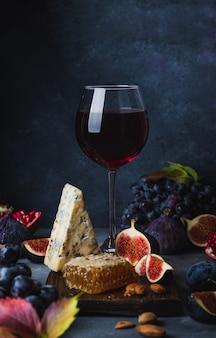 Бокал красного вина с виноградом, медом, сыром дорблю и фиги
