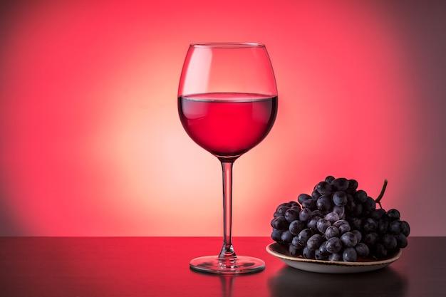 Бокал красного вина с виноградом на тарелке на красном заднем с копией пространства. дегустация винной концепции.