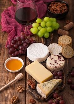 ボード上のさまざまなチーズと木製のテーブルの背景にブドウの選択と赤ワインのガラス。ブルースティルトン、レッドレスター、ブリーチーズとハチミツ。