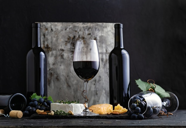 어두운 배경에 스낵과 치즈가 든 레드 와인 한 잔. 어두운 변덕스러운 검은색 콘크리트 배경에 유리와 레드 빈티지 와인 한 병.