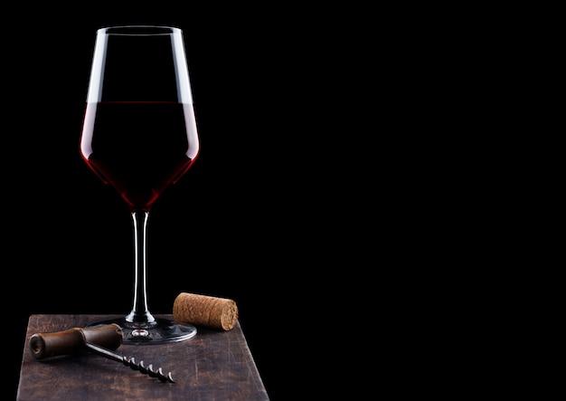 Стакан красного вина со старинным штопором и пробкой