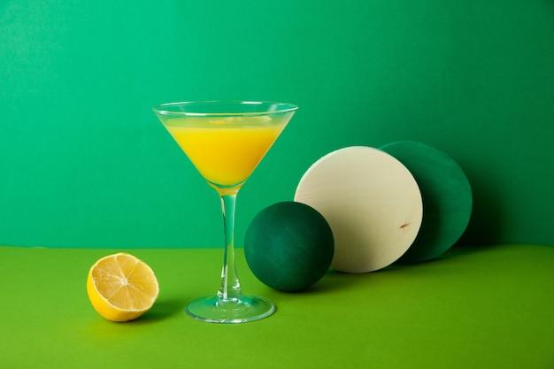 Стакан освежающего цитрусового коктейля с половинкой лимона на зеленом столе с различными декоративными элементами