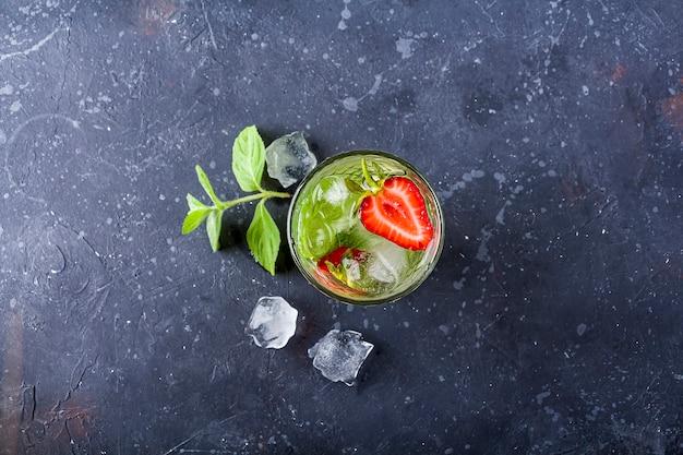 ストロベリーライムの夏のレモネードまたはアイスティーと一緒にさわやかなクールなデトックスドリンクのグラス