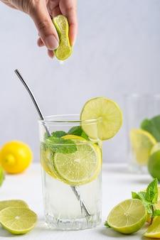 レモンスライスのさわやかなレモネードのグラススパークリングウォーターとミントをテーブルにストローで添え