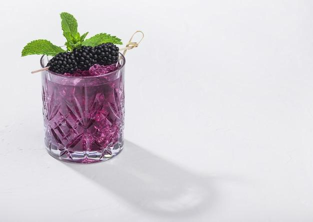 白い背景の上のブラックベリーとさわやかな夏の紫色のカクテルのガラス Premium写真