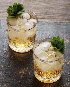 木製の背景、キューバリブレまたはロングアイランドアイスティーカクテルにラム酒のグラス