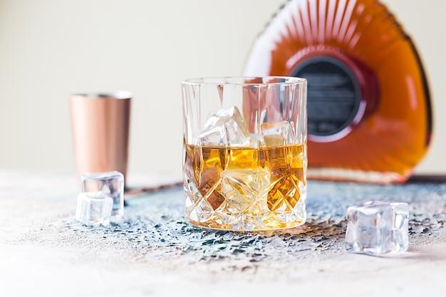 아이스 큐브, 병 및 구리 바 액세서리가있는 스카치 위스키 잔