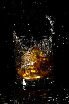 黒の背景にスプラッシュと氷とスコッチウイスキーのガラス