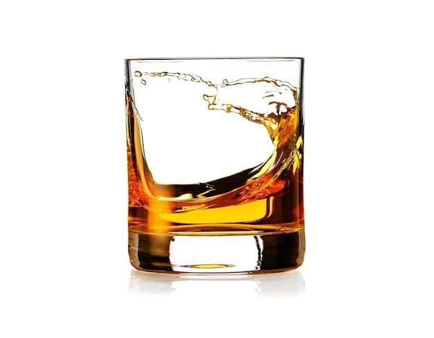 白い背景で隔離のスプラッシュとスコッチウイスキーのガラス