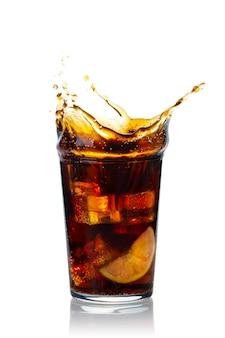 Стакан брызг напитка с ломтиком лимона и кубиками льда на белом фоне
