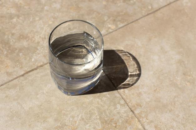 가혹한 햇빛, 긴 그림자, 테이블, 평면도에 테이블에 아직도 물의 유리. 건강 관리 개념, 상쾌한 여름 음료, 갈증 해소. 상위 뷰, 클로즈업, 텍스트 배치. 수평.
