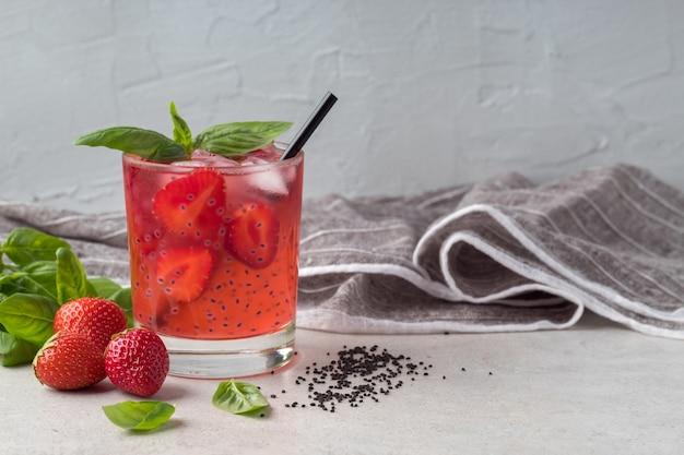 Стакан клубничного напитка с семенами базилика на сером столовом летнем напитке для детоксикации и похудения