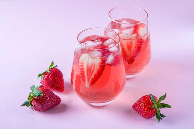 淡いピンクの背景にスパークリングワインとイチゴサングリアのガラス