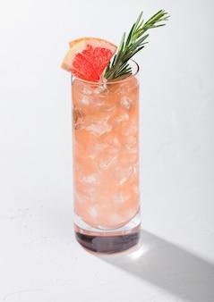 白い背景の上の角氷と夏の赤いグレープフルーツカクテルのガラス Premium写真